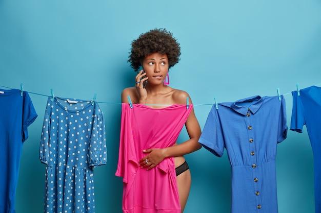 Plan d'une jeune femme songeuse à la peau foncée qui parle au téléphone, obtient des conseils sur quoi porter lors d'une réunion informelle, pose près d'une corde avec des robes, isolée sur un mur bleu. concept de vêtements.
