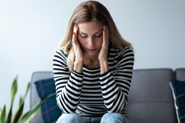 Plan d'une jeune femme souffrant de maux de tête assise sur le canapé du salon à la maison.