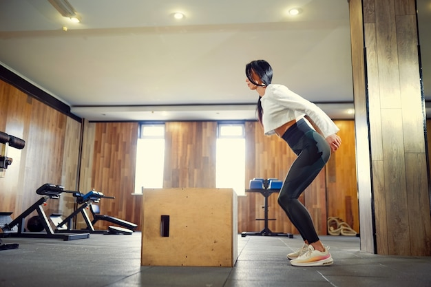 Plan d'une jeune femme travaillant avec une boîte à la salle de sport