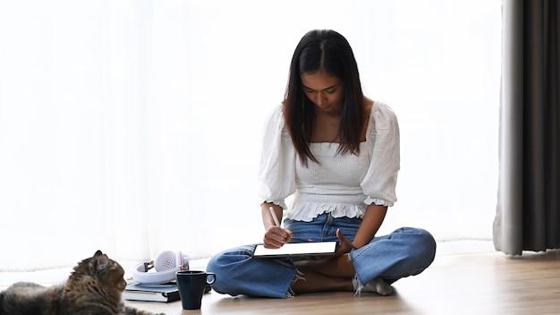 Plan d'une jeune femme utilisant une tablette numérique et assise sur le sol avec son chat dans le salon.