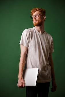 Plan d'un jeune hipster à tête de lecture barbu, tenant un ordinateur portable, détournant les yeux
