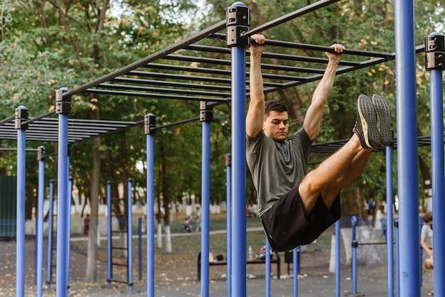 Plan d'un jeune homme faisant des creux sur les barres asymétriques.