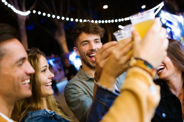 Plan de jeunes amis séduisants portant un toast avec de la bière au marché de la nourriture dans la rue.