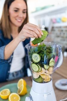 Plan d'une jolie jeune femme mettant des épinards dans le mélangeur pour préparer du jus de désintoxication dans la cuisine à la maison.