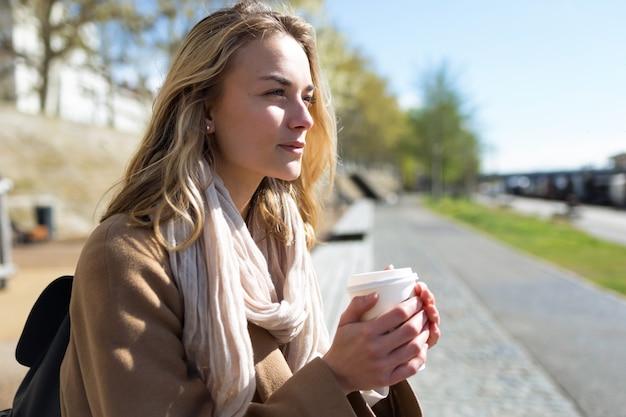 Plan d'une jolie jeune femme pensant et regardant de côté dans le parc.