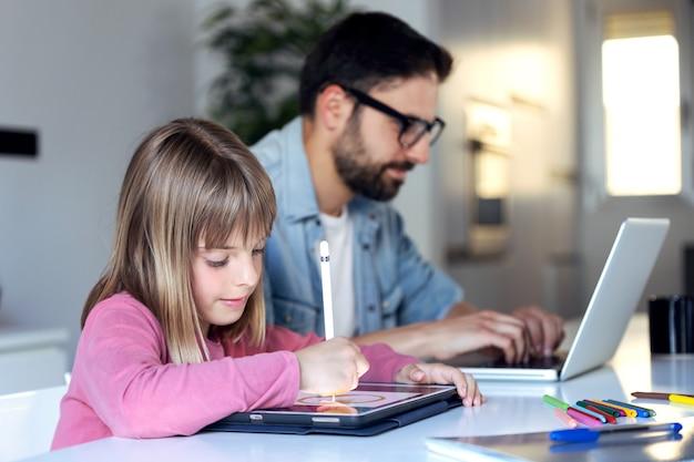 Plan d'une jolie petite fille dessinant sur sa tablette numérique pendant que son père travaille avec un ordinateur portable à la maison.