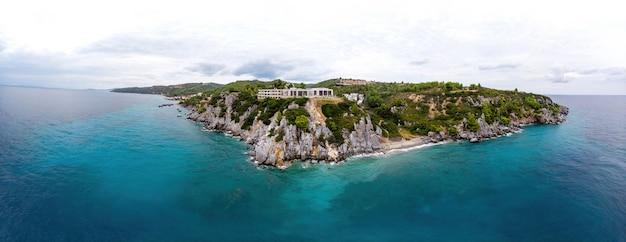 Plan large de la côte grecque de la mer égée, des bâtiments de loutra situés près des falaises rocheuses, de la verdure et de l'eau bleue. vue depuis le drone