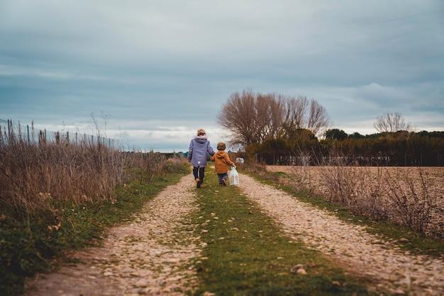 Plan large de deux garçons avec le dos tenant une lanterne marchant dans un chemin de campagne à l'automne
