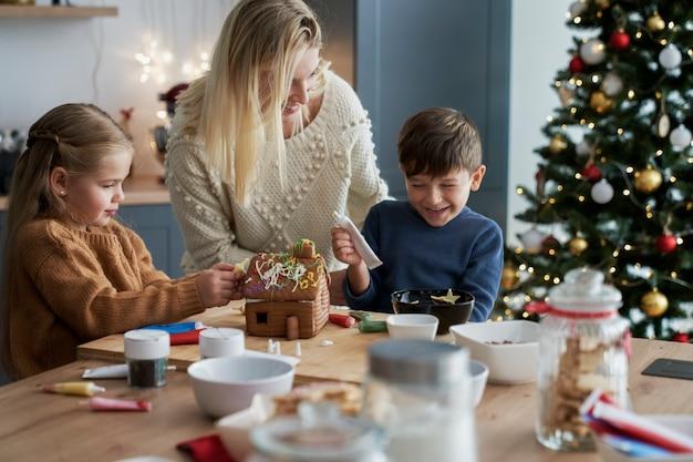 Plan large de la famille passant le temps de noël à la pâtisserie