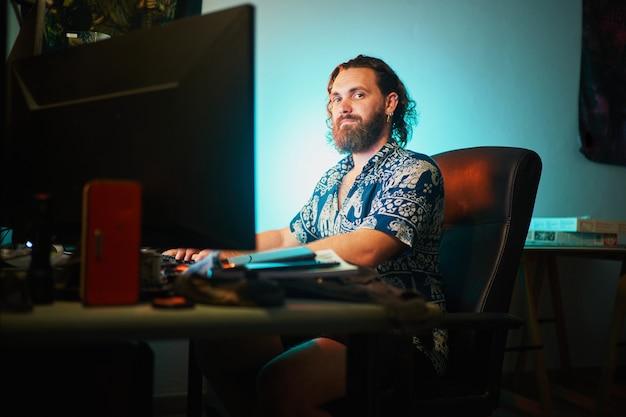 Plan large d'un homme barbu utilisant un ordinateur contre la lumière sarcelle assis sur une chaise regardant la caméra