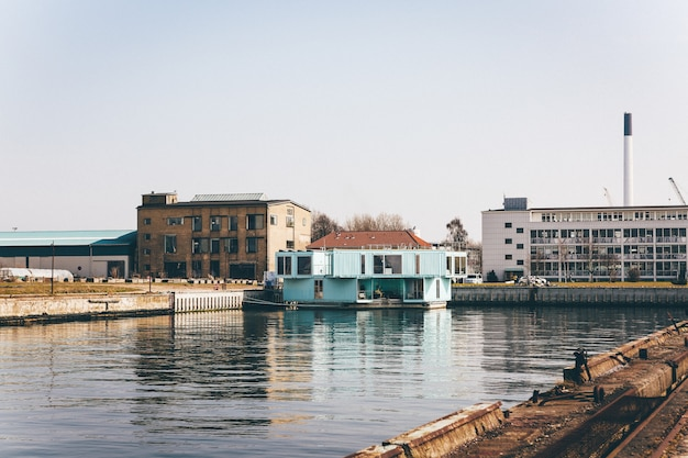 Plan large d'une maison bleu clair sur un quai sur le plan d'eau près de bâtiments sous un ciel clair