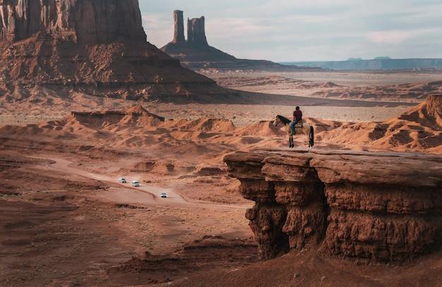 Plan large d'une personne sur un cheval près des falaises rouges sous un ciel bleu