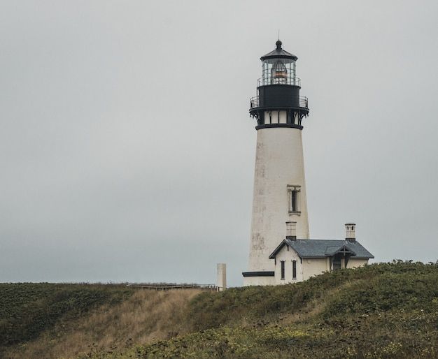 Plan large d'un phare blanc et noir près d'une maison au sommet d'une colline