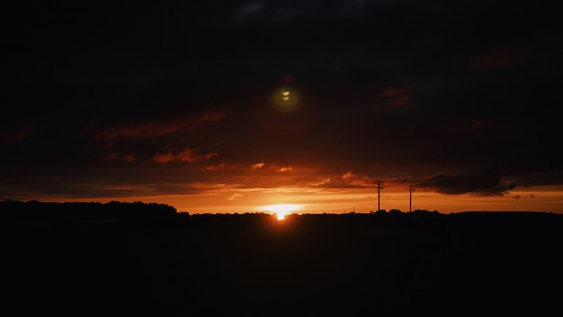 Plan large des silhouettes de collines dans la campagne au coucher du soleil