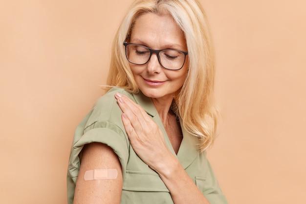 Plan latéral d'une femme adulte aux cheveux blonds regarde attentivement le bras avec du plâtre après l'injection de vaccin se protège du coronavirus porte des lunettes et s'habille isolé sur un mur beige