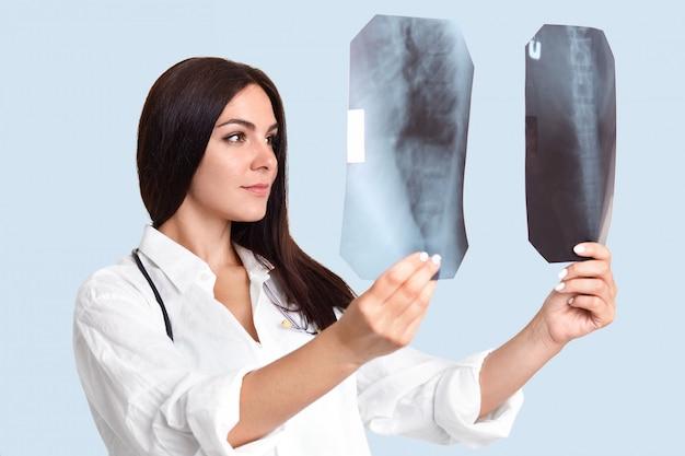 Plan latéral d'une femme médecin professionnelle compare deux images de rayons x d'un squelette