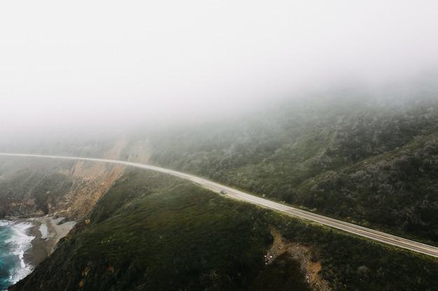 Plan lointain d'une route près de montagnes entourées d'arbres