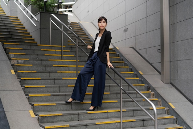 Plan long de belle femme d'affaires dans les escaliers