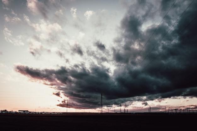 Plan long d'un ciel nuageux sombre au-dessus des tours d'antenne
