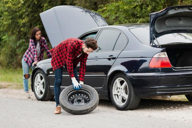Plan long d'un couple en train de réparer une voiture