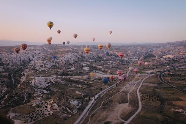 Plan long de divers montgolfières multicolores flottant dans le ciel