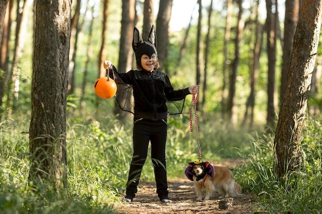 Plan long du petit garçon en costume de chauve-souris