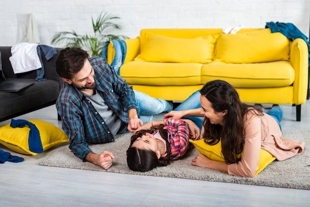 Plan long d'une famille heureuse et d'un salon en désordre
