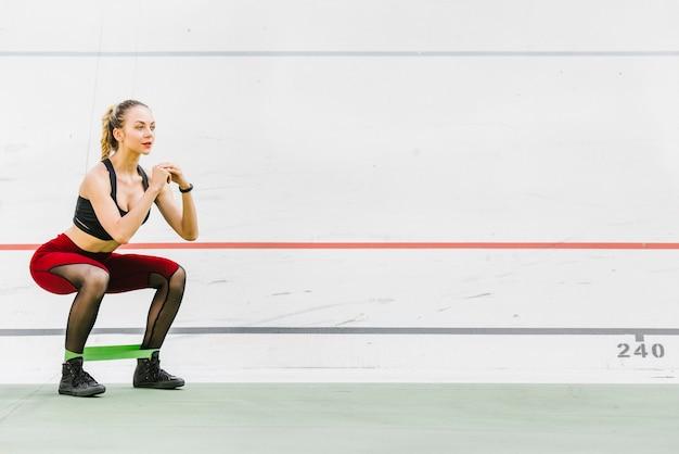 Plan long d'une femme faisant des squats