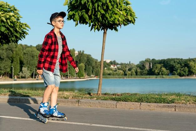 Plan long d'un garçon avec des patins à roues alignées