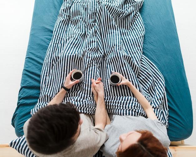 Plan long de gens assis dans son lit, buvant du café