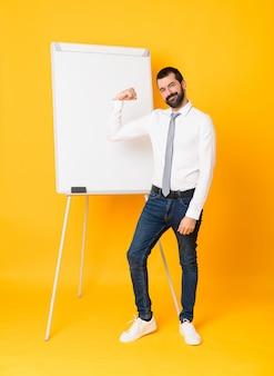 Plan long d'homme d'affaires donnant une présentation sur un tableau blanc sur fond jaune isolé faisant un geste fort