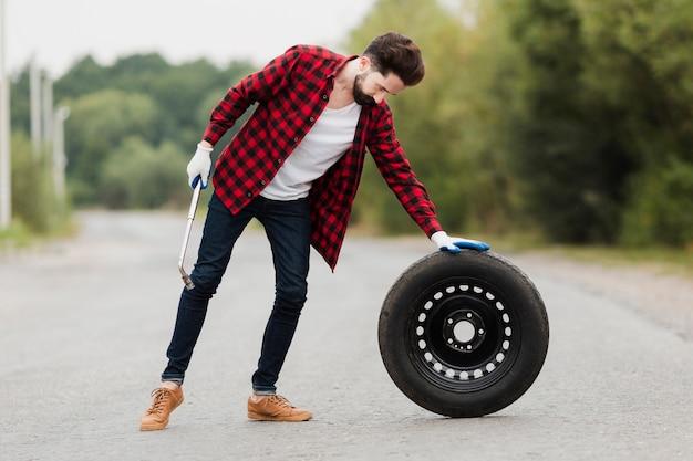 Plan long d'un homme avec une clé et un pneu
