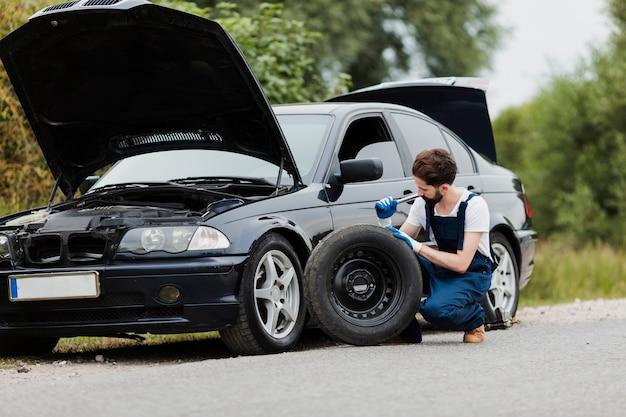 Plan long d'un homme échangeant un pneu