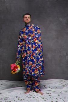 Plan long d'un homme en robe tenant des fleurs