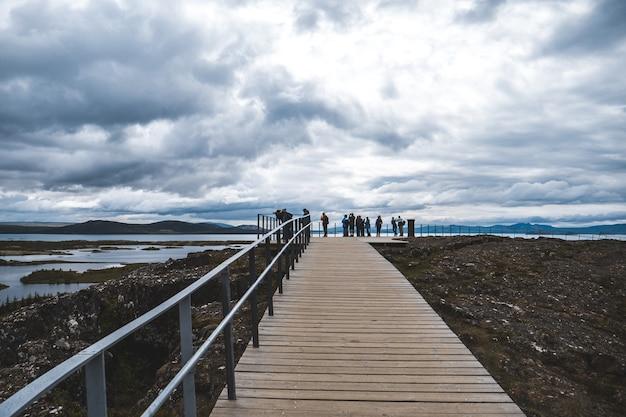 Plan long d'une promenade avec balustrade et touristes, donnant sur un lac par temps nuageux