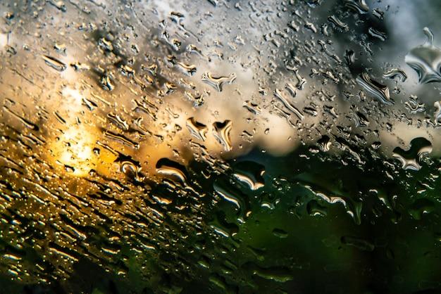 Plan macro sur une goutte d'eau sur une fenêtre après un jour de pluie, un fond abstrait et des textures
