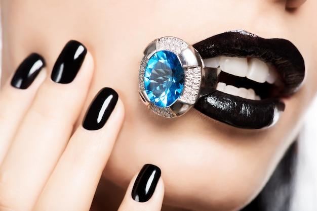 Plan macro sur les lèvres et les ongles d'une femme peints en noir de couleur vive