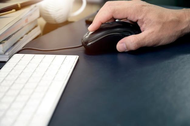 Plan d'une main d'homme tenant une souris alors qu'il travaillait au bureau avec un espace de copie.