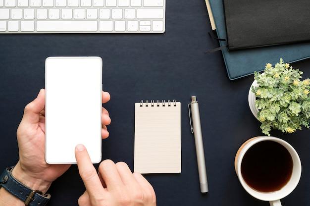 Plan de la main d'un homme touchant l'écran d'un smartphone alors qu'il travaillait au bureau