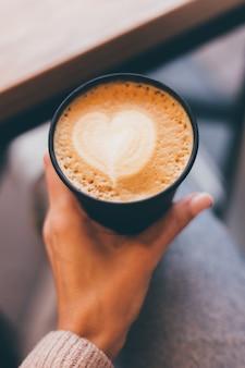 Plan de mains de femme tenant une tasse de café chaud avec un cœur en mousse.