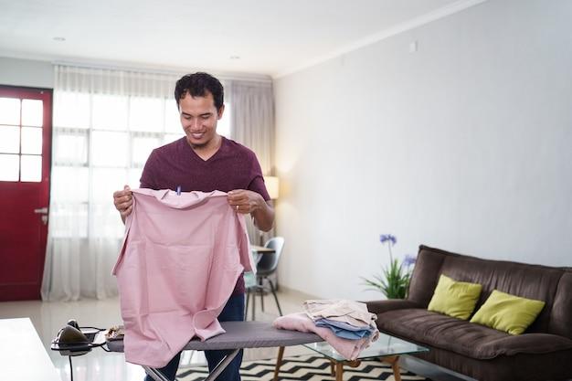 Plan d'un mari responsable ou d'un homme célibataire occupé à faire des travaux ménagers, repasse sa chemise le matin sur un bureau de repassage avant le travail,