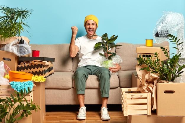 Plan d'un mec ravi serre le poing, pose devant un canapé, tient une plante d'intérieur enveloppée