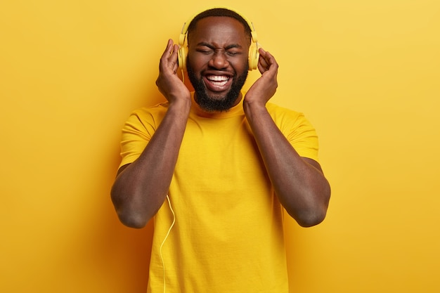 Plan monochrome d'un homme afro-américain ravi et heureux bénéficie d'un son parfait dans de nouveaux écouteurs, vêtu d'un t-shirt jaune, a du temps libre, se divertit avec de la musique. expression heureuse.