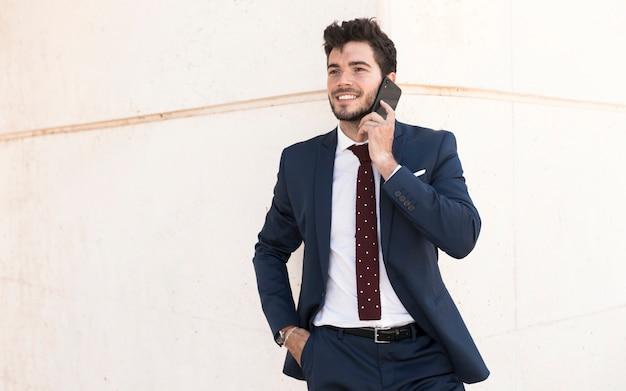 Plan moyen adulte en costume parlant au téléphone