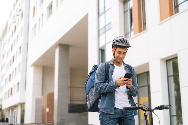 Plan moyen d'un beau courrier masculin joyeux avec un sac à dos thermo debout avec un vélo dans la rue de la ville et utilisant l'application de navigation sur téléphone. livreur à la recherche de l'adresse du client à la recherche d'un smartphone.