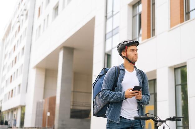 Plan moyen d'un beau courrier masculin sérieux avec un sac à dos thermo debout avec un vélo dans la rue de la ville et utilisant l'application de navigation sur téléphone. livreur à la recherche de l'adresse du client à la recherche d'un smartphone.