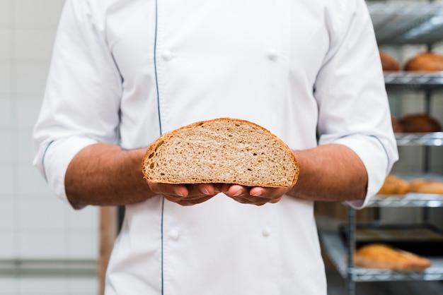 Plan moyen d'un boulanger tenant un pain coupé en deux dans la main