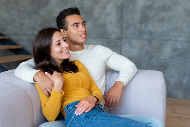Plan moyen d'un couple devant la télé