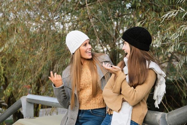 Plan moyen de deux femmes parlant dans le parc