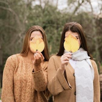 Plan moyen de deux personnes se couvrant le visage de feuilles d'automne
